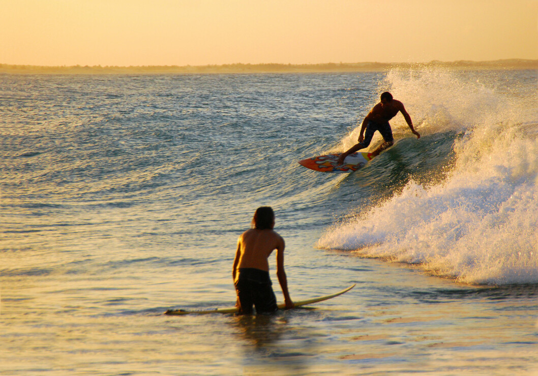 SURFING: Surfere bruker aldri vest, men er bundet til brettet som er et effektivt flytemiddel.