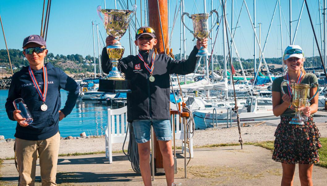 33 ÅR ETTER: 33 år etter at pappa Jon Eriksen kunne heve seierstrofeene i Optimist-NM, kunne Henrik Løset Eriksen gjøre det samme. Til venstre Philip Forslund og til høyre Hedvig Doksrød.