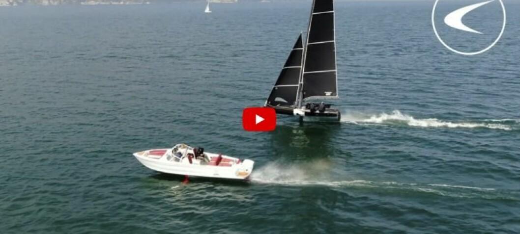 Seil- mot motorbåt på foiler