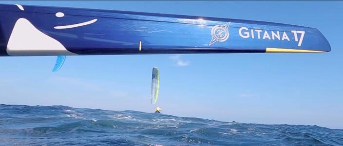 En kiter blir liten under baugen på den enorme trimaranen.