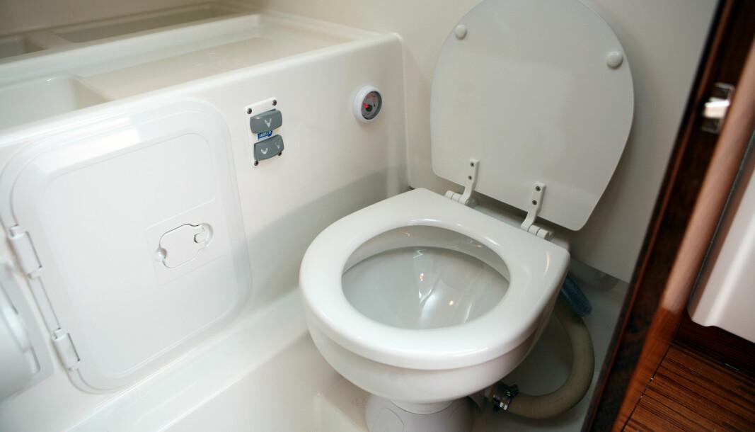KONVERTERT: Den gamle toalettskålen plassert på den nye, elektriske pumpen. Toalettlokket kan åpnes fritt og har en bra vinkel mot skottet. Holder man inne den øverste knappen på betjeningspanelet, så sørger automatikken for tømming og spyling av toalettet.